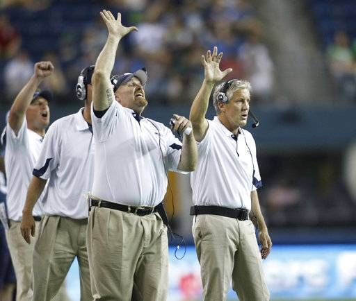 FILE - In this Aug. 14, 2010, file photo, Seattle Seahawks coaches Dan Quinn, defensive line, left, and head coach, Pete Carroll, right, gesture on the sideline during an NFL preseason game against the Tennessee Titans, in Seattle. The scheme that carried the Seahawks to consecutive Super Bowls (2013-14) has become increasingly popular around the league. Los Angeles Chargers defensive coordinator Gus Bradley, Atlanta defensive coordinator Marquand Manuel, San Francisco defensive coordinator Robert Saleh, Atlanta head coach Dan Quinn and Jacksonville defensive coordinator Todd Wash all spent time in Seattle under Carroll.