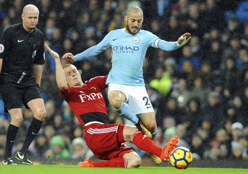 Manchester City's David Silva, right, vies for the ball with Watford's Ben Watson during the English Premier League soccer match between Manchester City and Watford at Etihad stadium, in Manchester, England, Tuesday, Jan. 2, 2018.