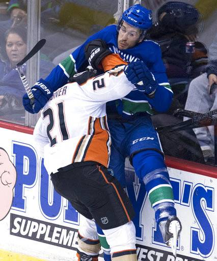 Anaheim Ducks center Chris Wagner (21) puts Vancouver Canucks defenseman Michael Del Zotto (4) into the boards during the third period of an NHL hockey game Tuesday, Jan. 2, 2018, in Vancouver, British Columbia. (Jonathan Hayward/The Canadian Press via AP)