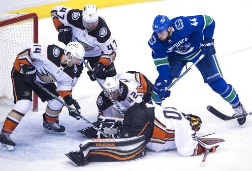 Anaheim Ducks' Josh Manson (42), Adam Henrique (14) and Hampus Lindholm (47) help goaltender Ryan Miller (30) contain the puck from Vancouver Canucks defenseman Erik Gudbranson (44)  during the third period of an NHL hockey game Tuesday, Jan. 2, 2018, in Vancouver, British Columbia. (Jonathan Hayward/The Canadian Press via AP)