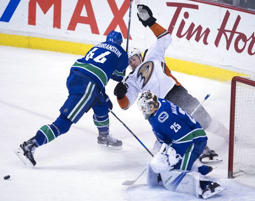 Vancouver Canucks defenseman Erik Gudbranson (44) clears Anaheim Ducks left wing Nick Ritchie (37) from in front of Canucks goaltender Jacob Markstrom (25) during the third period of an NHL hockey game Tuesday, Jan. 2, 2018, in Vancouver, British Columbia. (Jonathan Hayward/The Canadian Press via AP)