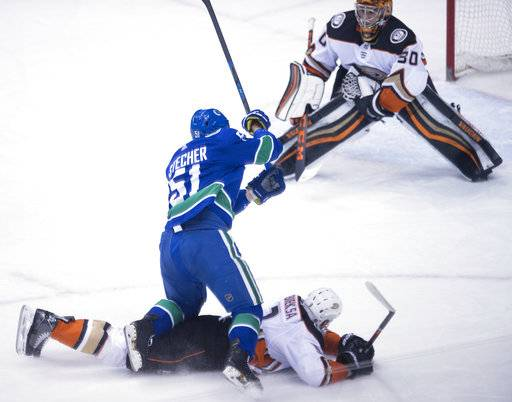 Anaheim Ducks defendeman Kevin Bieksa (3) stops Vancouver Canucks defedceman Troy Stecher (51) from getting a shot on Ducks goaltender Ryan Miller (30) during the second period of an NHL hockey game Tuesday, Jan. 2, 2018, in Vancouver, British Columbia. (Jonathan Hayward/The Canadian Press via AP)
