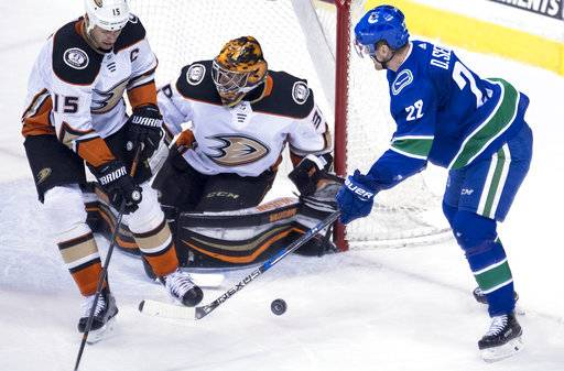 Anaheim Ducks center Ryan Getzlaf (15) watches as Vancouver Canucks left wing Daniel Sedin (22) fails to get a shot past Anaheim Ducks goaltender Ryan Miller (30) during the second period of an NHL hockey game Tuesday, Jan. 2, 2018, in Vancouver, British Columbia. (Jonathan Hayward/The Canadian Press via AP)