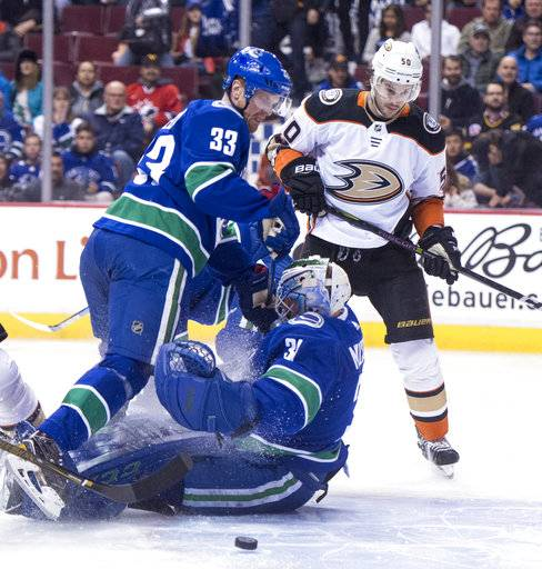 Vancouver Canucks center Henrik Sedin (33) bangs into Canucks goaltender Anders Nilsson (31) as Anaheim Ducks center Antoine Vermette (50) watches during the first period of an NHL hockey game Tuesday, Jan. 2, 2018, in Vancouver, British Columbia. (Jonathan Hayward/The Canadian Press via AP)