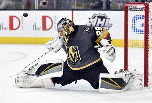 Vegas Golden Knights goalie Marc-Andre Fleury deflects the puck on a shot by the Nashville Predators during the first period of an NHL hockey game Tuesday, Jan. 2, 2018, in Las Vegas.