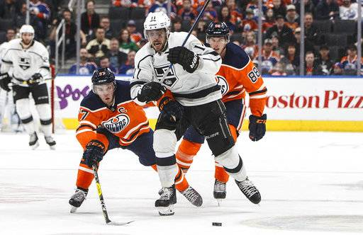 Los Angeles Kings' Anze Kopitar (11) is chased by Edmonton Oilers' Connor McDavid (97) and Brandon Davidson (88) during the third period of an NHL hockey game in Edmonton, Alberta, Tuesday Jan. 2, 2018. (Jason Franson/The Canadian Press via AP)
