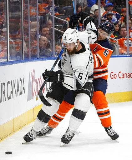 Los Angeles Kings' Jake Muzzin (6) and Edmonton Oilers' Adam Larsson (6) battle for the puck during the second period of an NHL hockey game in Edmonton, Alberta, Tuesday, Jan. 2, 2018. (Jason Franson/The Canadian Press via AP)