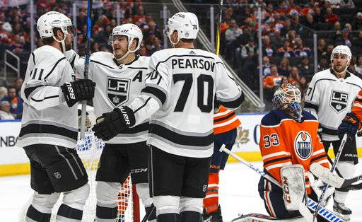Los Angeles Kings' Anze Kopitar (11), Dustin Brown (23) and Tanner Pearson (70) celebrate a goal on Edmonton Oilers goalie Cam Talbot (33) during the third period of an NHL hockey game in Edmonton, Alberta, Tuesday Jan. 2, 2018. (Jason Franson/The Canadian Press via AP)