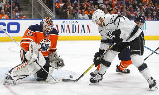 Los Angeles Kings' Trevor Lewis (22) is stopped by Edmonton Oilers' goalie Cam Talbot (33) during the first period of an NHL hockey game, Tuesday, Jan. 2, 2018, in Edmonton, Alberta. (Jason Franson/The Canadian Press via AP)
