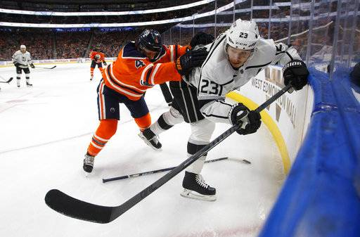 Los Angeles Kings' Dustin Brown (23) is checked by Edmonton Oilers' Kris Russell (4) during the first period of an NHL hockey game, Tuesday, Jan. 2, 2018, in Edmonton, Alberta. (Jason Franson/The Canadian Press via AP)