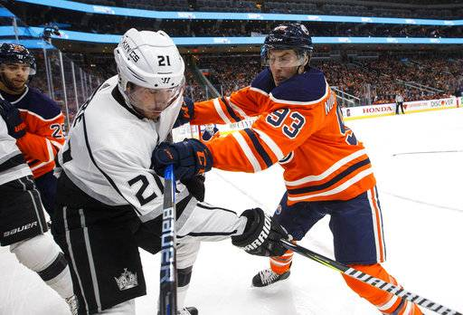Los Angeles Kings' Nick Shore (21) is checked by Edmonton Oilers' Ryan Nugent-Hopkins (93) during the first period of an NHL hockey game, Tuesday, Jan. 2, 2018, in Edmonton, Alberta. (Jason Franson/The Canadian Press via AP)