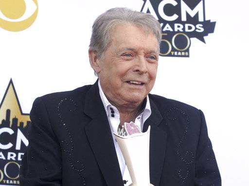 FILE - In this April 19, 2015 file photo, Mickey Gilley poses with the triple crown award on the red carpet at the 50th annual Academy of Country Music Awards at AT&T Stadium in Arlington, Texas. Country music artist Gilley and his son were injured in a car accident in Texas, but both are recovering after minor injuries. A statement from Gilley's publicist on Thursday, Jan. 4, 2018, said the two were injured Wednesday when their car rolled over. (Photo by Jack Plunkett/Invision/AP, File)