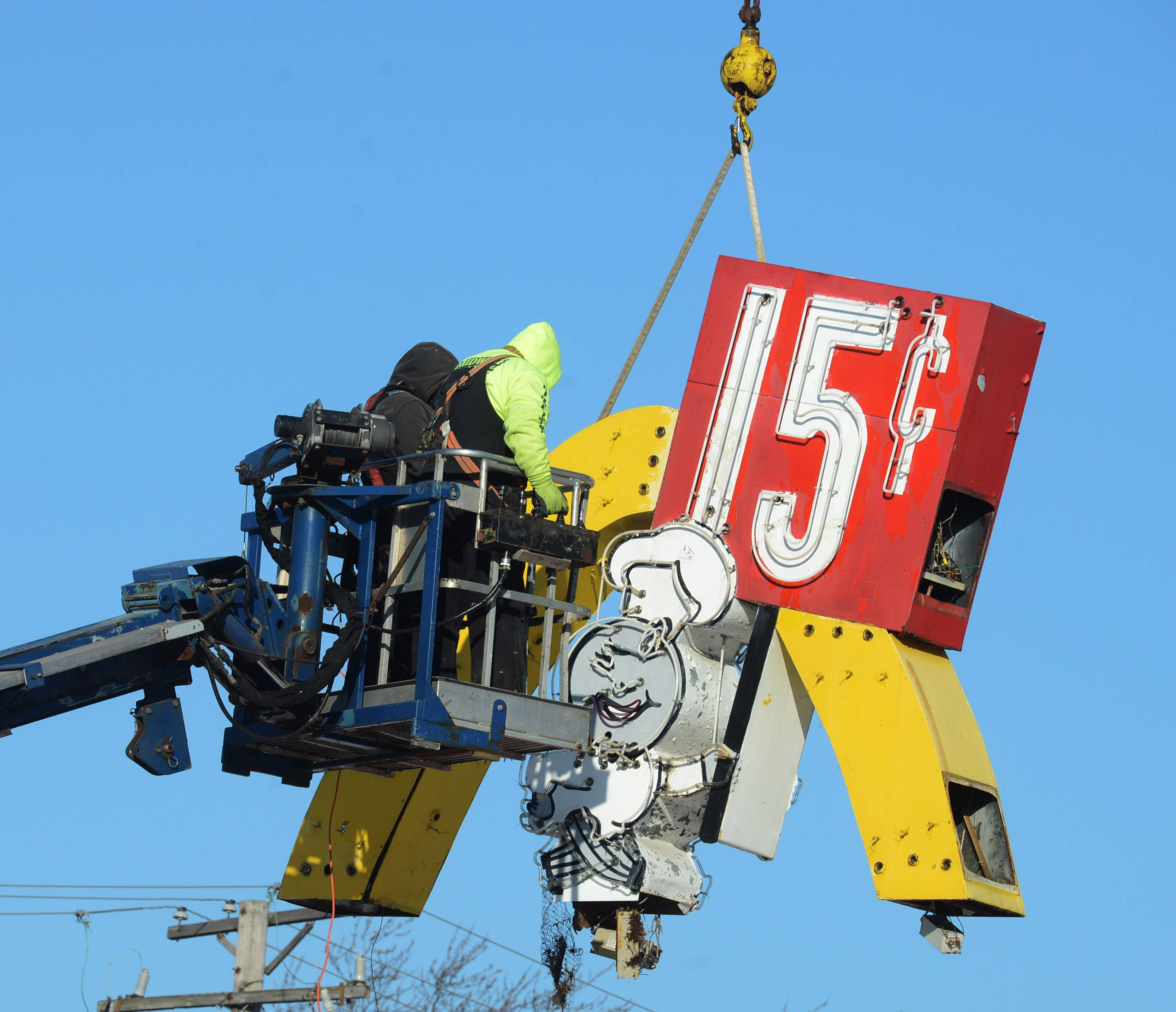 "The top ""Speedee"" portion of the original McDonald's sign is lifted by a crane Thursday outside the replica restaurant in Des Plaines."