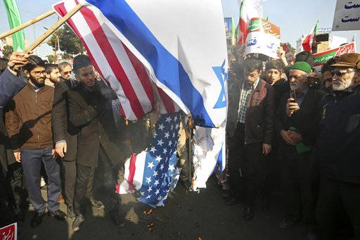In this photo provided by Tasnim News Agency, Iranian demonstrators burn representations of U.S. and Israeli flags in a pro-government rally in the northeastern city of Mashhad, Iran, Thursday, Jan. 4, 2018. The strength of protests shaking Iran was unclear on Thursday after a week of unrest that killed at least 21 people, with fewer reports of demonstrations as government supporters again took to the streets in several cities and towns. (Nima Najafzadeh,Tasnim News Agency via AP)