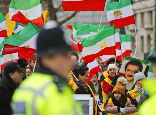 Police officers guard the Anglo-Iranian communities, supporters of Iran's democratic opposition, the National Council of Resistance of Iran (NCRI) and main organised opposition movement PMOI, as they hold a rally opposite the entrance of 10 Downing Street in London, Thursday, Jan. 4, 2018, in solidarity with the nationwide anti-regime protests in Iran.