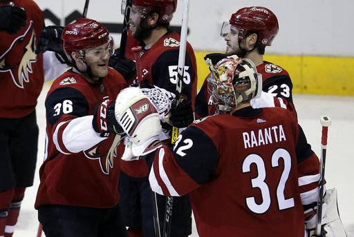 Arizona Coyotes right wing Christian Fischer (36) celebrates with Antti Raanta (32) after scoring in overtime against the Nashville Predators during an NHL hockey game, Thursday, Jan. 4, 2018, in Glendale, Ariz. The Coyotes won 3-2. (AP Photo/Rick Scuteri)
