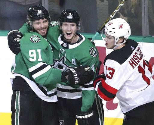 Dallas Stars Tyler Seguin (91) and John Klingberg (3) celebrate Seguin's goal as New Jersey Devils Nico Hischier (13) skates past during the second period of an NHL hockey game Thursday, Jan. 4, 2018, in Dallas. (Louis DeLuca/The Dallas Morning News via AP)