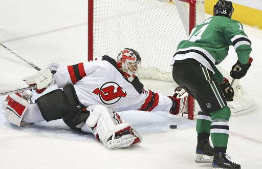 New Jersey Devils goaltender Cory Schneider (35) gives up a goal to Dallas Stars' Tyler Seguin, not seen, as Stars left wing Jamie Benn (14) skates past the net during the second period of an NHL hockey game Thursday, Jan. 4, 2018, in Dallas. (Louis DeLuca/The Dallas Morning News via AP)