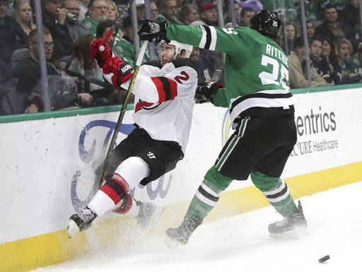 New Jersey Devils defenseman John Moore (2) crashes into the boards next to Dallas Stars right wing Brett Ritchie (25) during the first period of an NHL hockey game in Dallas, Thursday, Jan. 4, 2018.