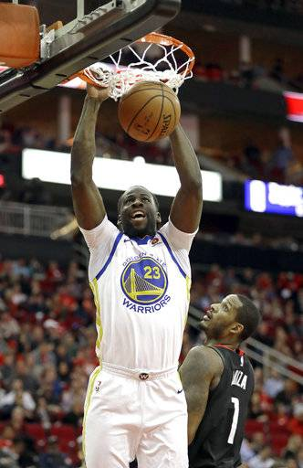 Golden State Warriors' Draymond Green (23) dunks the ball as Houston Rockets' Trevor Ariza (1) watches during the first half of an NBA basketball game Thursday, Jan. 4, 2018, in Houston.