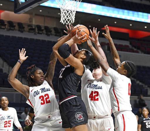 South Carolina forward A'ja Wilson (22) takes a shot past Mississippi forwards Kate Rodgers (32), Shelby Gibson (42) and guard Chyna Nixon (0) during the first half of an NCAA college basketball game in Oxford, Miss., Thursday, Jan. 4, 2018. (AP Photo/Thomas Graning)
