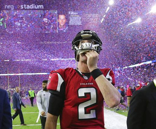 FILE - In this photo taken Feb. 5, 2017, file photo, , Atlanta Falcons quarterback Matt Ryan reacts after losing Super Bowl 51 as the screen flashes New England Patriots quarterback Tom Brady and confetti flies in Houston. Seven of the 12 teams that are in the NFL playoffs have never won the big game, matching the largest group of playoff-bound squads with not-so-Super pedigrees since the 1999 season. (Curtis Compton/Atlanta Journal-Constitution via AP, File)