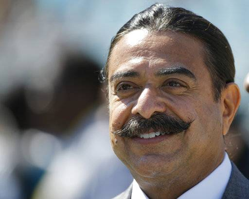 "FILE - In this Oct. 19, 2014, file photo, Jacksonville Jaguars team owner Shad Khan watches players warm up before an NFL football game against the Cleveland Browns in Jacksonville, Fla. Khan felt the organization ""lacked football IQ� in previous years. So Khan hired two-time Super Bowl-winning coach Tom Coughlin to handle football-related decisions. With Coughlin calling the shots, the Jaguars made the postseason for the first time since 2007 and will host a playoff game for the first time since January 2000. (AP Photo/Stephen B. Morton, File)"