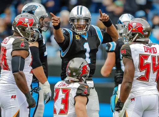 FILE - In this Sunday, Dec. 24, 2017, file photo, Carolina Panthers' Cam Newton (1) signals his first down in the middle of the Tampa Bay Buccaneers defense during the first half of an NFL football game in Charlotte, N.C. Carolina has three times run for more than 200 yards in a game this season, and that bodes well for the playoffs where the ground game is magnified. (AP Photo/Bob Leverone, File)