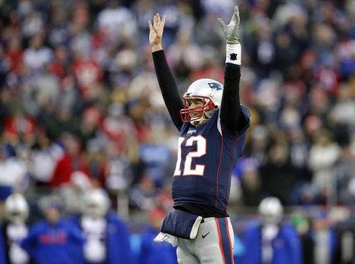 FILE - In this Sunday, Dec. 24, 2017, file photo, New England Patriots quarterback Tom Brady celebrates a touchdown by running back Dion Lewis during the second half of an NFL football game against the Buffalo Bills,, in Foxborough, Mass. Brady and the Patriots again top the AFC playoff field. (AP Photo/Charles Krupa, File)