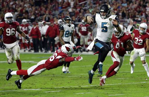 FILE - In this Nov. 26, 2017, file photo, Jacksonville Jaguars quarterback Blake Bortles (5) runs in a touchdown past Arizona Cardinals safety Budda Baker (36) and strong safety Antoine Bethea (41) during the second half of an NFL football game in Glendale, Ariz. The Jaguars, Bills and Titans all ended long droughts to return to the playoff party.
