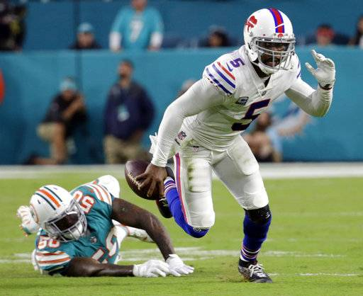 FILE - In this Sunday, Dec. 31, 2017, file photo, Buffalo Bills quarterback Tyrod Taylor (5) escapes a tackle by Miami Dolphins defensive end Andre Branch (50), during the first half of an NFL football game in Miami Gardens, Fla. The Jaguars, Bills and Titans all ended long droughts to return to the playoff party.