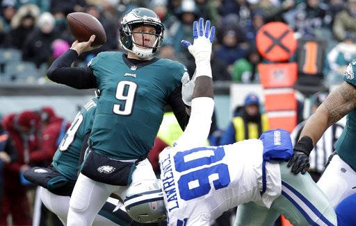 FILE - In this Dec. 31, 2017, file photo, Philadelphia Eagles' Nick Foles (9) throws a pass over Dallas Cowboys' DeMarcus Lawrence (90) during the first half of an NFL football game in Philadelphia. The Eagles earned the top seed in the NFC playoffs for the first time since 2004. (AP Photo/Chris Szagola, File)