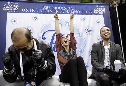 Adam Rippon, center, cheers his scores next to coach Rafael Arutyunyan, left, during the men's short program at the U.S. Figure Skating Championships in San Jose, Calif., Thursday, Jan. 4, 2018. (AP Photo/Marcio Jose Sanchez)