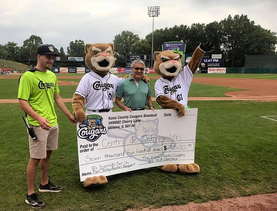 The Kane County Cougars and Minor League Baseball Charities present Jaime Garcia, executive director of Centro de Informacion, with a charitable donation Sept. 4. The proceeds were raised through the online jersey auction held during the Es Divertido Ser Un Fan campaign.