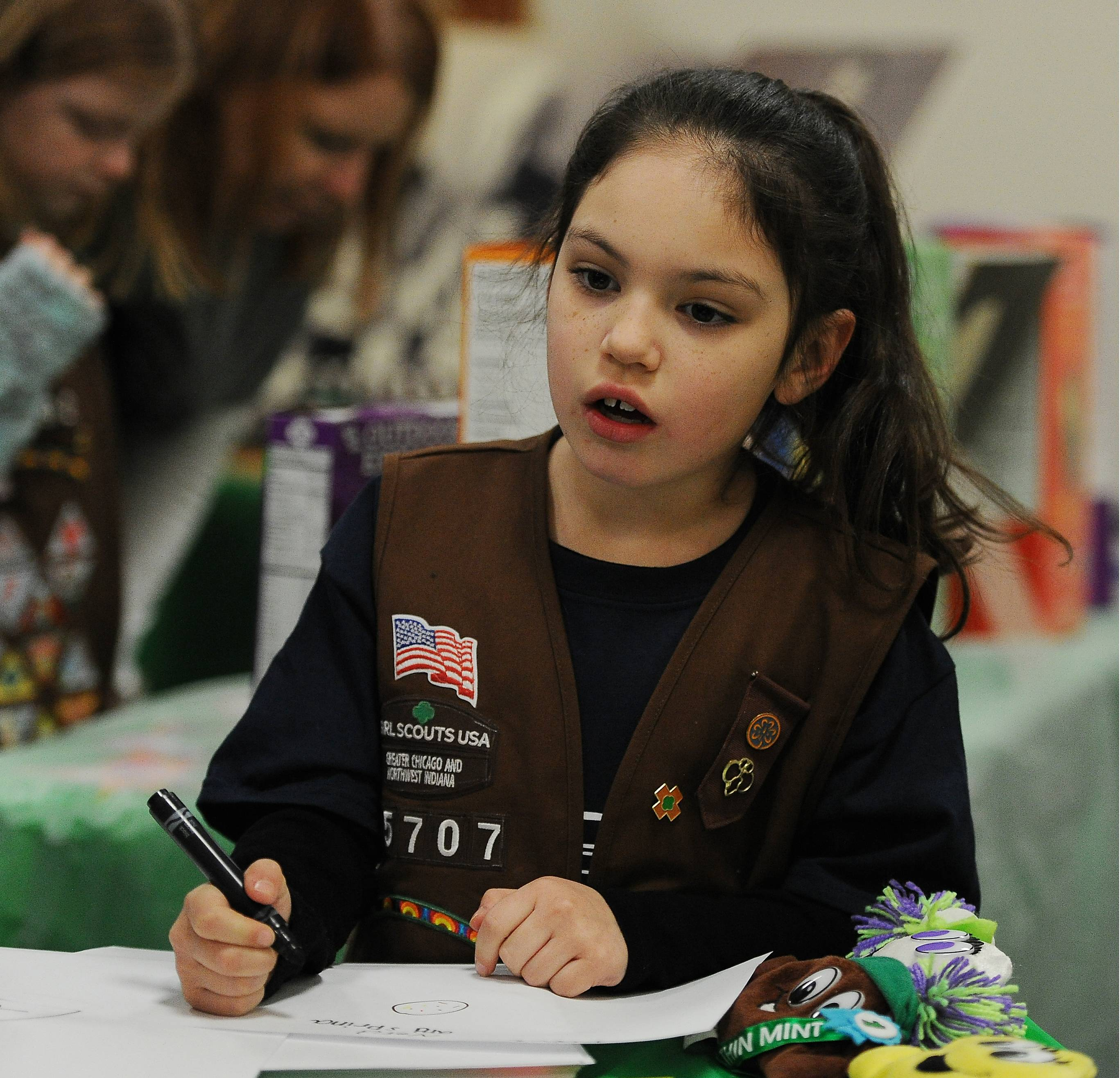 Isabel Enciso, 7, of Round Lake's Brownie Troop 45707, thinks about the art design she just created, which depicts what the cookie of the future will look like according to her imagination as part of Girl Scouts annual cookie sale kickoff at the Allstate Arena on Saturday.