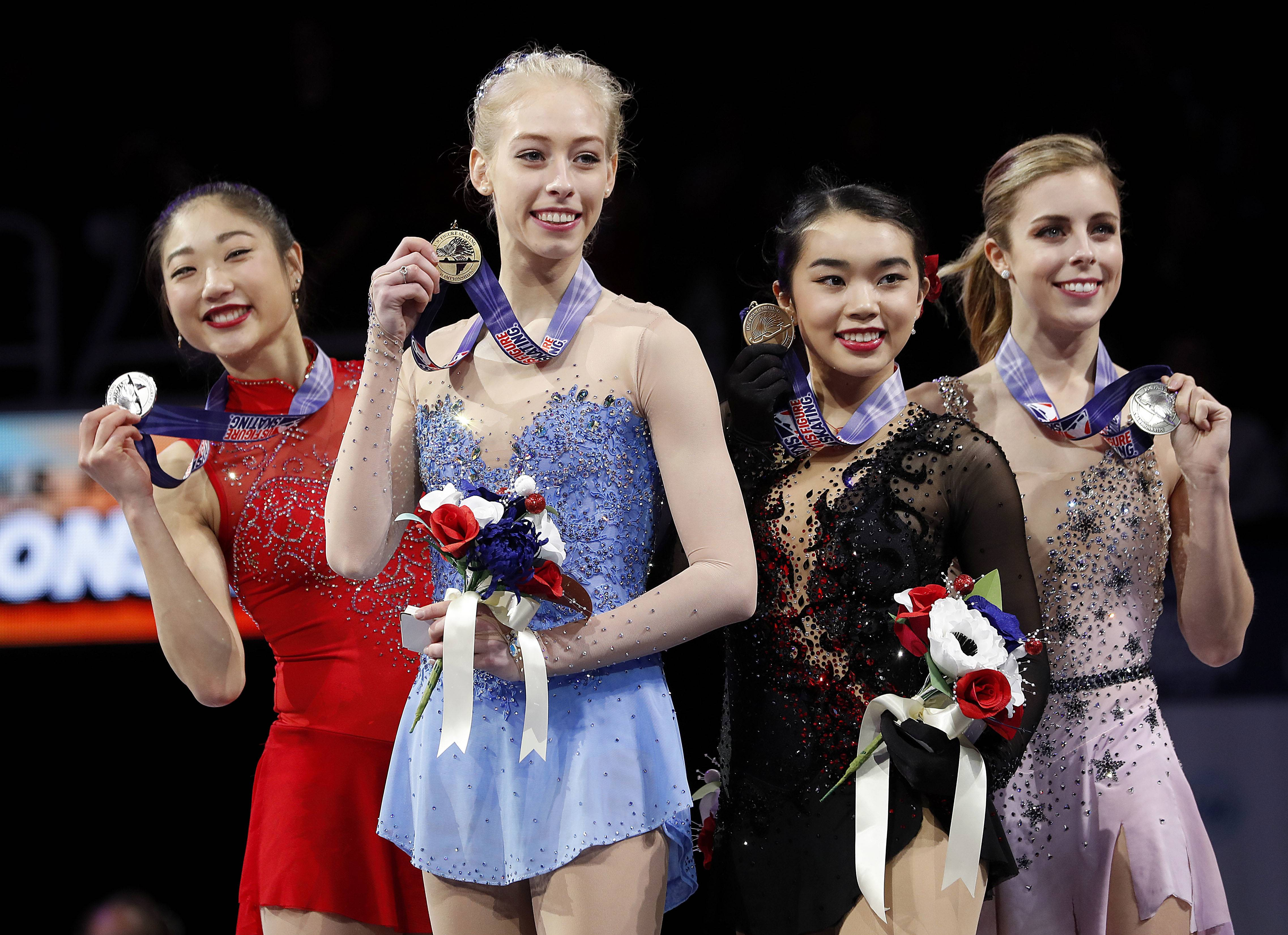 Bradie Tennell, foreground, poses Friday after winning the women's free skate event with second place finisher Mirai Nagasu, left, third place finisher Karen Chen, second from right, and fourth place finisher Ashley Wagner.