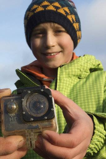 Britain's William Etherton holds a camera on the North Sea island of Suederoog, Germany, Saturday, Jan. 6, 2018. The English boy has been reunited in Germany with a video camera he lost four months ago on the other side of the North Sea. News agency dpa reported that the camera was handed back to the 10-year-old Saturday on Suederoog, a small island off Germany's western coast a little south of the Danish border. (Christian Charisius/dpa via AP)