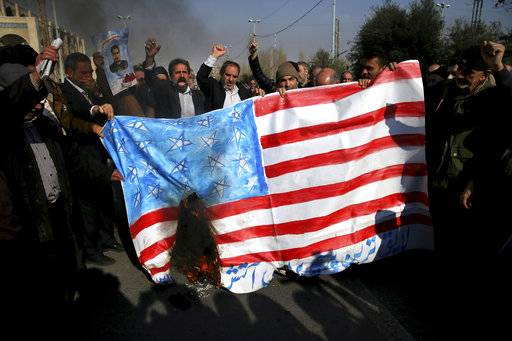 Iranian worshippers chant slogans while they burn a representation of U.S. flag during a rally against anti-government protestors after the Friday prayer ceremony in Tehran, Iran, Jan. 5, 2018. A hard-line Iranian cleric has called on Iran to create its own indigenous social media apps, blaming them for the unrest that followed days of protest in the Islamic Republic over its economy. (AP Photo/Ebrahim Noroozi)