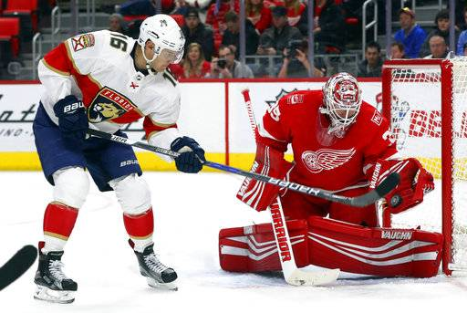 Detroit Red Wings goaltender Jimmy Howard (35) stops a shot from Florida Panthers center Aleksander Barkov (16) in the first period of an NHL hockey game Friday, Jan. 5, 2018, in Detroit. (AP Photo/Paul Sancya)