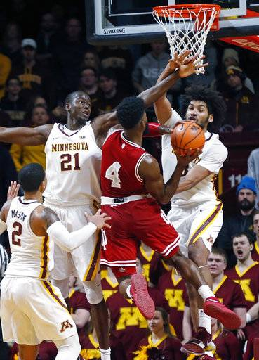 Indiana's Robert Johnson (4) lays up as Minnesota's Bakary Konate, left, and Jordan Murphy defend in the second half of an NCAA college basketball game, Saturday, Jan. 6, 2018, in Minneapolis. Illinois won 75-71. Johnson led Illinois with 28 points. (AP Photo/Jim Mone)