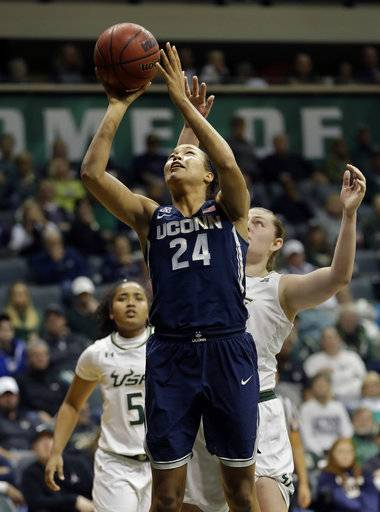 Connecticut forward Napheesa Collier (24) shoots after getting around South Florida center Alyssa Rader and guard Vanessa Blagmon (5) during the third quarter of an NCAA college basketball game Saturday, Jan. 6, 2018, in Tampa, Fla. UConn won 100-49. (AP Photo/Chris O'Meara)