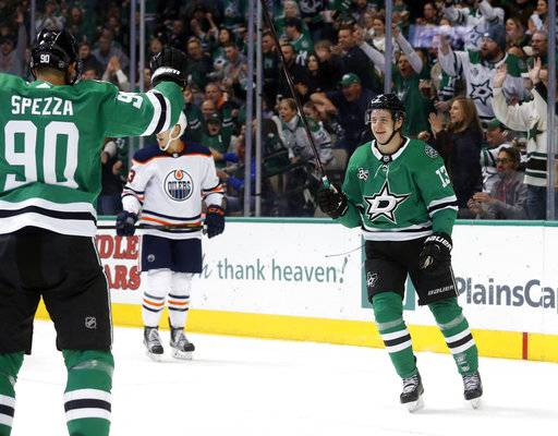 Dallas Stars center Jason Spezza (90) celebrates a goal by Stars center Mattias Janmark (13) as Edmonton Oilers defenseman Matt Benning (83) skates away during the second period of an NHL hockey game in Dallas, Saturday, Jan. 6, 2018. (AP Photo/Michael Ainsworth)