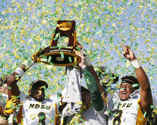North Dakota State safety Tre Dempsey (3), head coach Chris Klieman and running back Bruce Anderson (8) celebrate after defeating James Madison 17-13 in the FCS championship NCAA college football game at Toyota Stadium in Frisco, Texas, Saturday, Jan. 6, 2017. (Vernon Bryant/The Dallas Morning News via AP)
