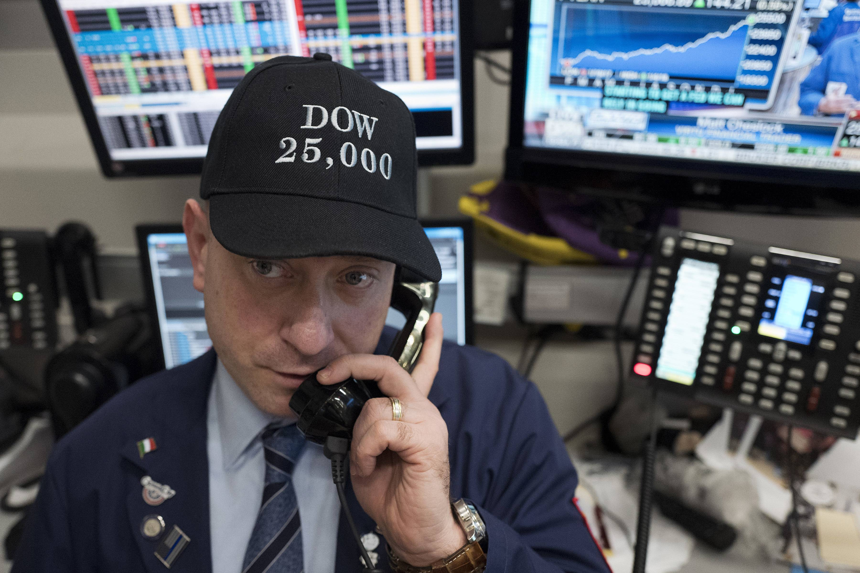 Vincent Pepe, a commodities broker with ICAP Corp., wears a Dow 25,000 hat to work at the New York Stock Exchange, Thursday, Jan. 4, 2018. There's no doubt the U.S. economy and Wall Street have momentum heading into Trump's second year as president, but worker pay remains frustratingly flat.