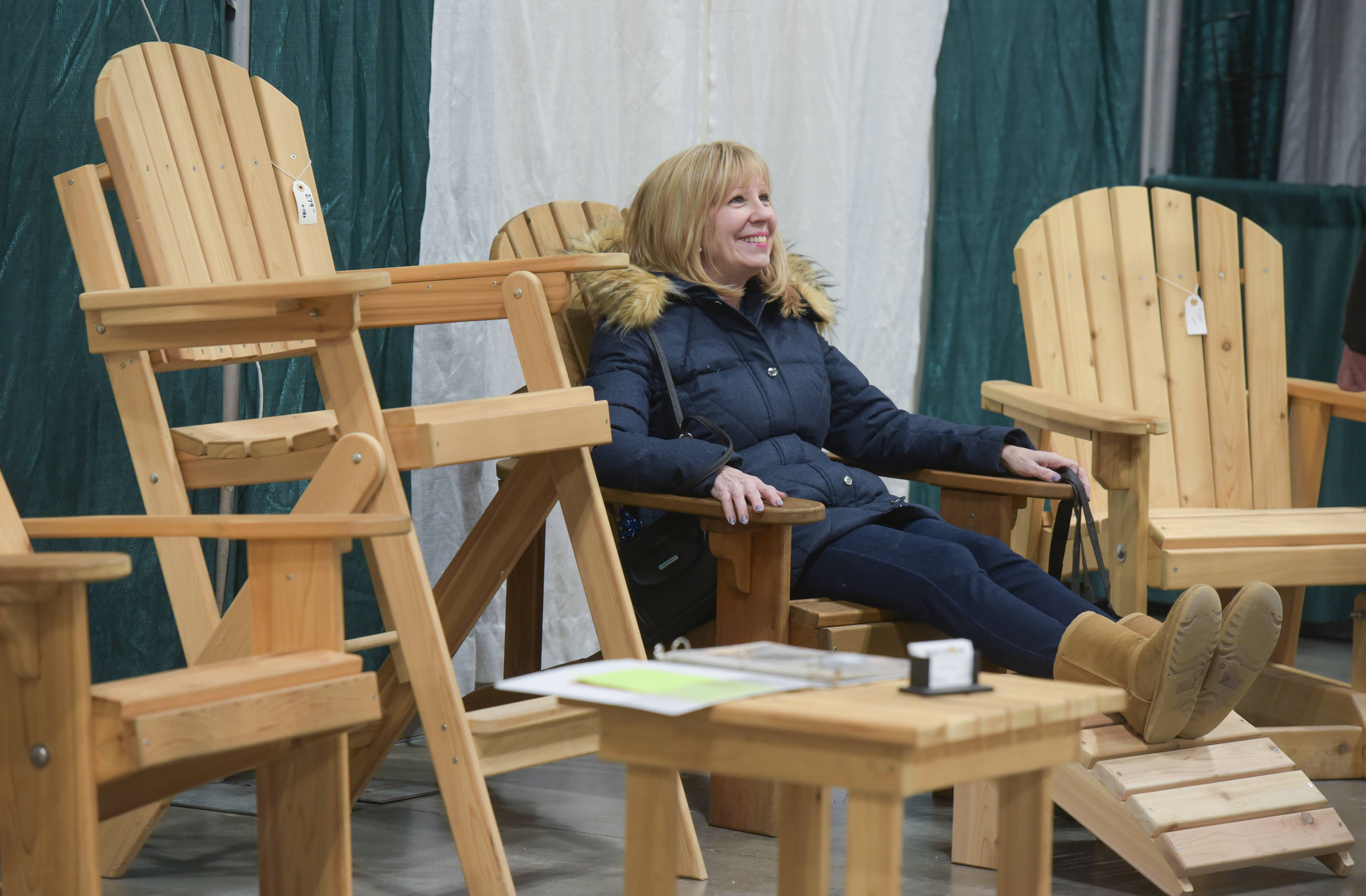 Cindy Mak of Aurora lounges in an Adirondack chair, made by Wade Thompson, owner of Wade's World of Woodworking in Batavia, during the annual Schaumburg Lake Home & Cabin Show at the Schaumburg Convention Center on Sunday.