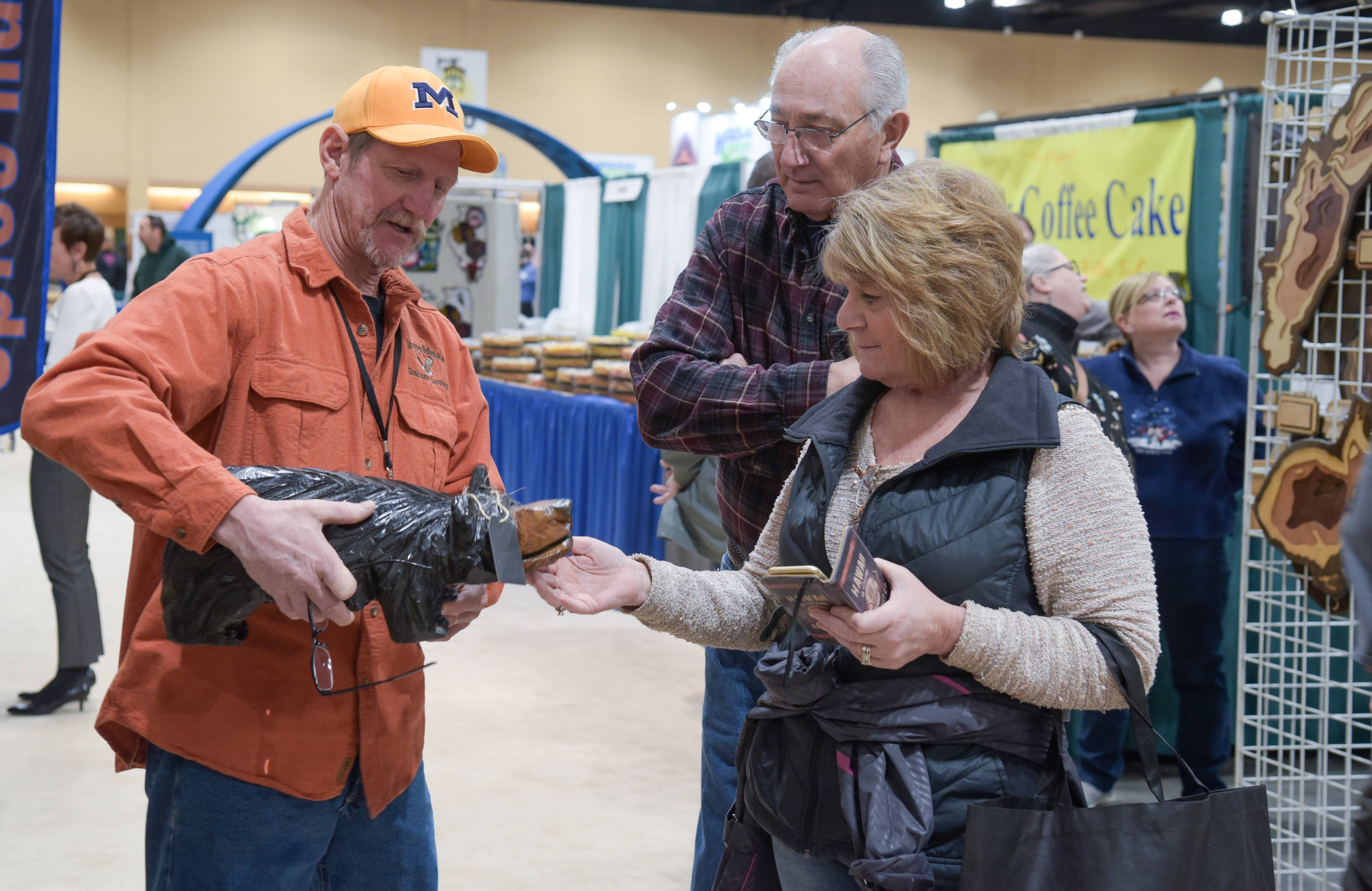 Chainsaw artist Dan Hoffman of Unique Ideas Chainsaw Art talks with Chuck and Debbie Mueller of Johnsburg during the annual Schaumburg Lake Home & Cabin Show at the Schaumburg Convention Center on Sunday.