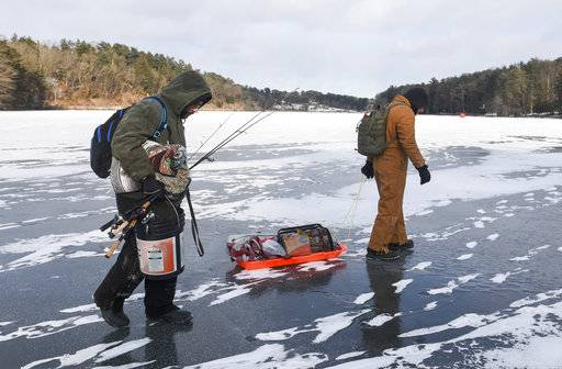 Chris Fidler, left, of Halifax, and Ben Reigert, of Reading, walk out onto the ice at Sweet Arrow Lake, to fish on Saturday, Jan. 6, 2018, in Pine Grove, Pa. Freezing temperatures since December 26 have made for ideal ice fishing conditions. (David McKeown/Republican-Herald via AP)