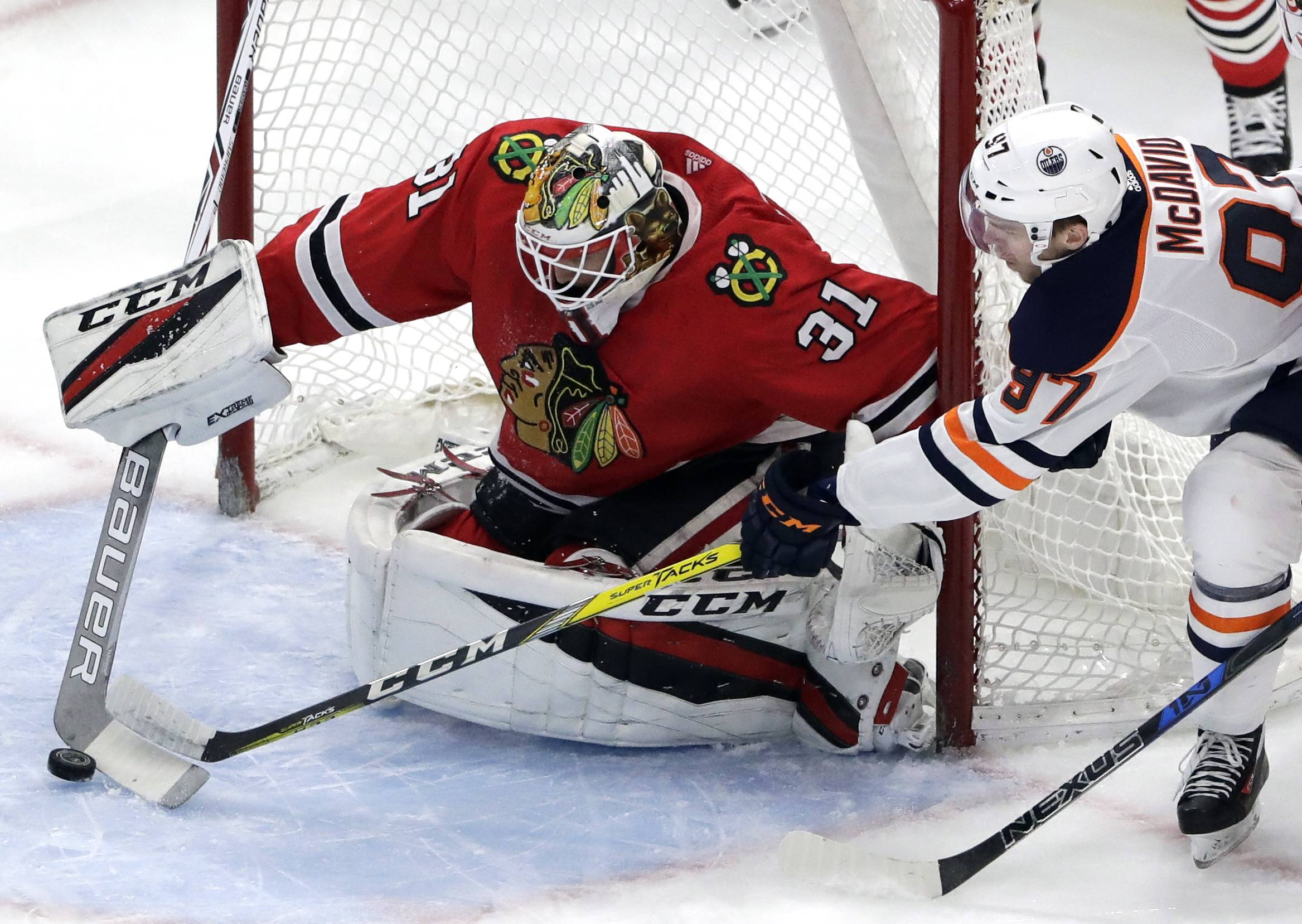 Chicago Blackhawks goalie Anton Forsberg, left, blocks a shot by Edmonton Oilers center Connor McDavid during the first period of an NHL hockey game Sunday, Jan. 7, 2018, in Chicago.