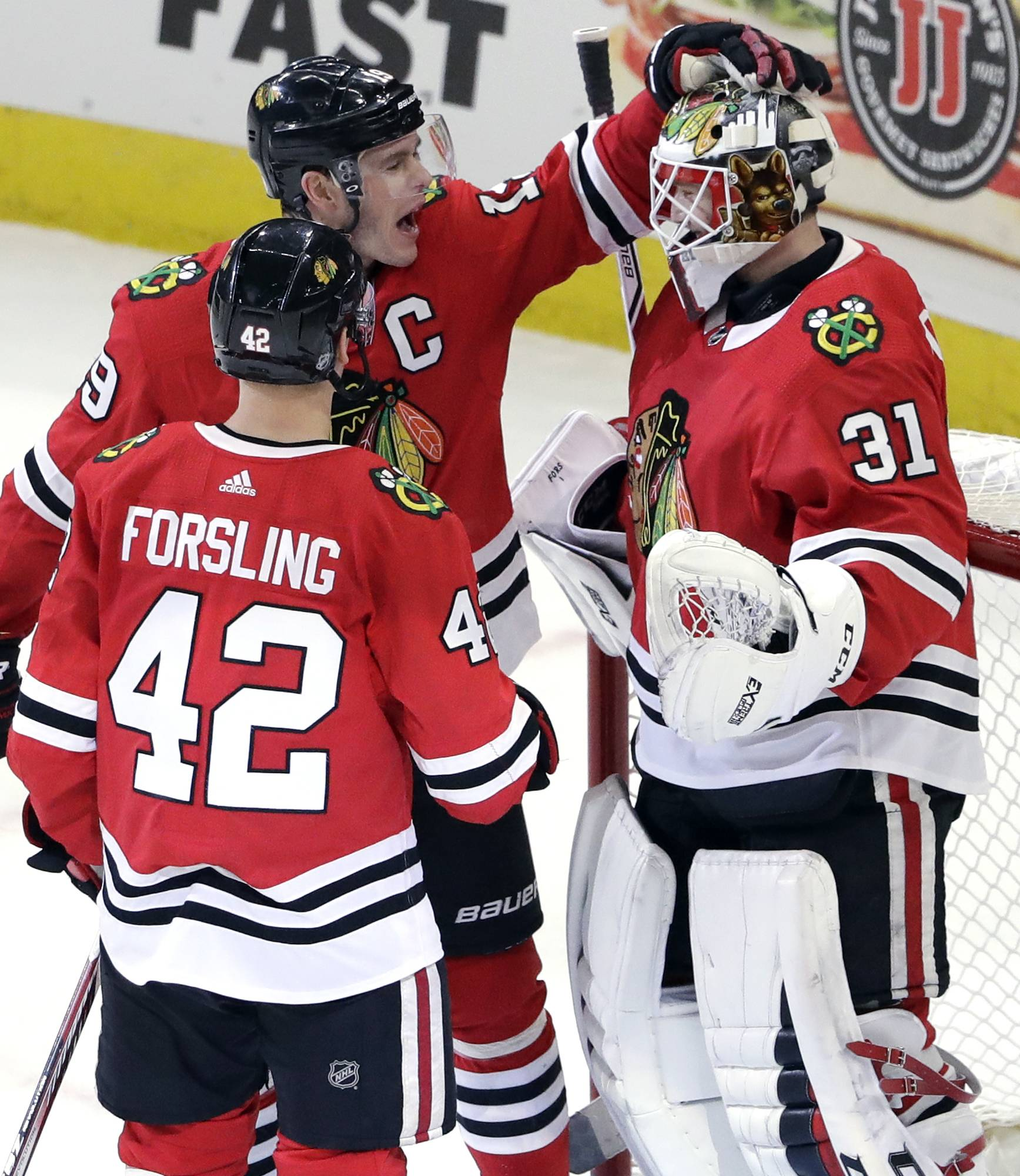 Chicago Blackhawks goalie Anton Forsberg, right, celebrates with center Jonathan Toews and defenseman Gustav Forsling (42) after they defeated the Edmonton Oilers in an NHL hockey game Sunday, Jan. 7, 2018, in Chicago.