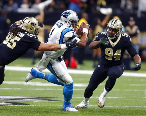 Carolina Panthers quarterback Cam Newton (1) carries between New Orleans Saints defensive tackle Tyeler Davison (95) and defensive end Cameron Jordan (94) in the first half of an NFL football game in New Orleans, Sunday, Jan. 7, 2018. (AP Photo/Butch Dill)